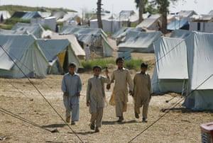 Pakistan Swat exodus: Pakistani boys walk through a refugee camp at Swabi, in northwest Pakistan