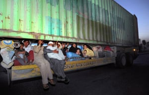 Pakistan Swat exodus: Displaced Pakistanis hitch a ride underneath a container truck