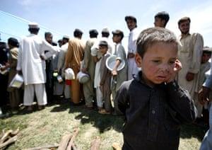 Pakistan Swat exodus: Children wait to get food at a refugee camp in Mardan