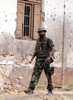Tamil Tigers surrender: sri lankan soldier patrols the jaffna suburb in 2000