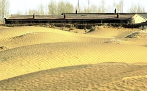 Minqin China: Photo shows an abandoned house facing the approaching desert