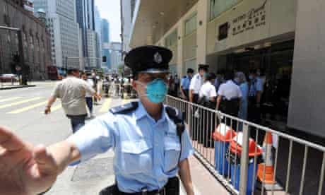 A policeman guards Hong Kong's Metropark hotel, which is under swine flu quarantine