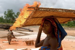 Shell in the Niger Delta: Women dry tapioca beside flames from Shell's Utorogu flow station.