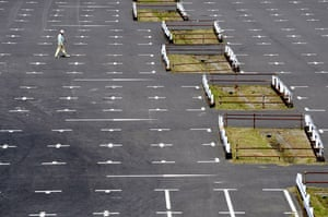 20 May 2009: Tokyo, Japan: A worker walks through an empty parking space