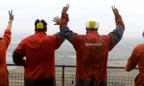 Greenpeace activists stand on top of the Kingsnorth coal plant