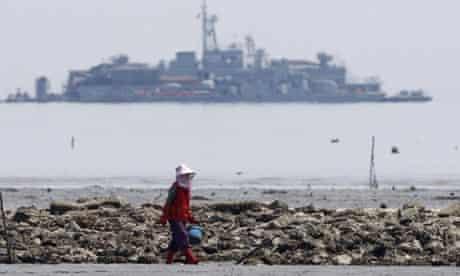 A South Korean woman walks along an oyster field