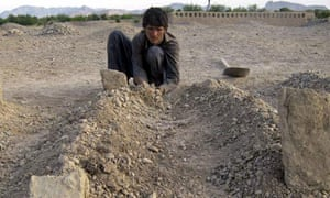 An Afghan places dirt over the grave of one of his family members after air strikes in Gangabad
