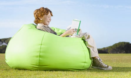 Young boy on a bean bag reading outdoors