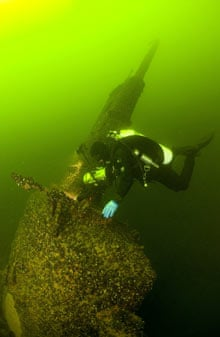 A diver examines the periscope tower of a Soviet submarine sunk in 1940