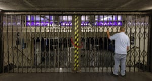 Tube strike: A man examines the closed shutters at Pimlico Underground Station