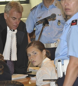 Meredith Kercher trial: manda Knox is escorted by a police officer as she meets her lawyer