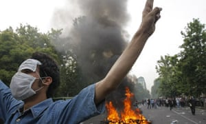 Supporter of Mir Hossein Mousavi in front of a burning police motorbike