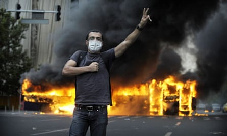 Smoke billows from a burning bus behind a supporter of Mir Hossein Mousavi