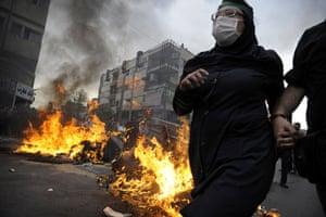 Riots in Tehran: Supporters of Mir Hossein Mousavi run past burning debris