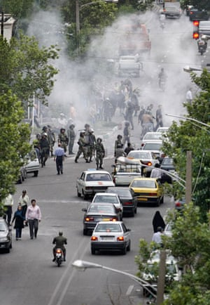 Riots in Tehran: Iranian riot police stand in front of a cloud of tear gas