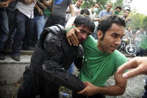 Riots in Tehran: A protestor helps evacuate an injured Iranian riot-police officer