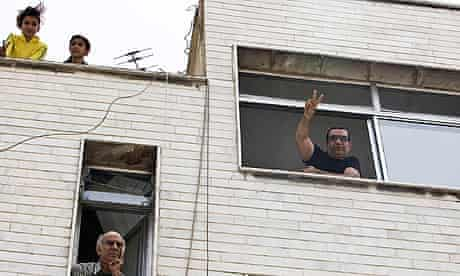 A supporter of Mir Hussein Mousavi flashes the victory sign as he watches protests in Tehran.