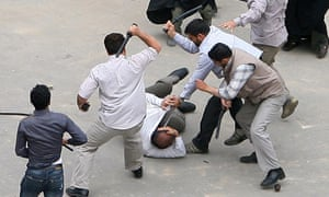 Iranian security agents beat a supporter of Mir Hossein Mousavi