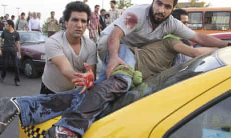 A man seriously injured at a rally supporting Mir Hossein Mousavi lies on the back of a taxi