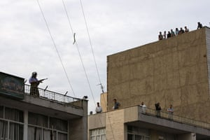 Iran protests: A member of a pro-government militia stands guard on a rooftop