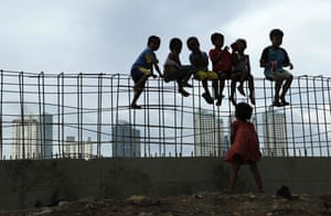 24 hours in pictures: Children sit on iron bars at a construction site in Jakarta