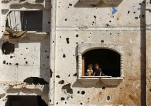 24 hours in pictures: Palestinian children look out of window of damaged house in Rafah
