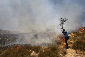 24 hours in pictures: A Palestinian man tries to put out a fire in field