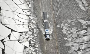 A semi-truck and trailer drives through floodwater and ice slabs