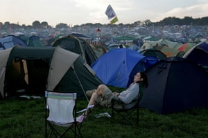 First day at Glastonbury: A reveller taking it easy in a sea of tents at Glastonbury