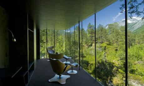 Glass building with chairs overlooking forest in Norway