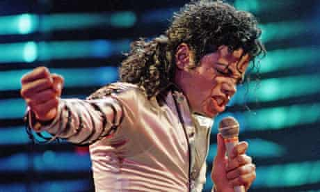 Michael Jackson in white singing into a microphone