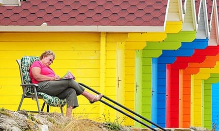 A woman enjoys the hot weather outside beach huts in North Bay, Scarborough