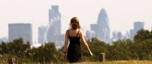 UK weather update: A woman walks past a view of the City of London in Richmond Park