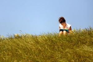 Heatwave: A woman reads a book as people enjoy the sunshine on Primrose Hill, London