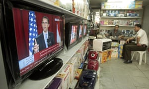 Palestinians watch President Barack Obama's speech in Cairo at a shop in Gaza City.