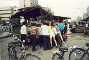 Tiananmen protests 1989: After the tank patrol passes, civilians push buses back at a roadblock