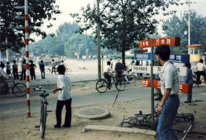 Tiananmen protests 1989: Civilians watch a military armoured vehicle drive by