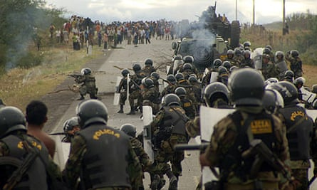 Police officers take up positions during clashes with protesters in Bagua province, Peru.
