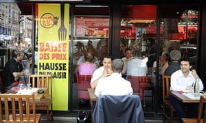 "Customers have lunch near a sign which reads ""fall of prices and rise of pleasure"" in Paris."