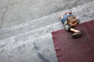 24hours in pictures: An Uighur baby crawls on his hands and knees on stairs