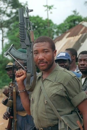 Charles Taylor: 1990: Rebel leader Charles Taylor holds his Soviet-made AK-47