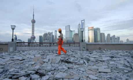 A labourer walks on the bank of the Huang Pu River  in Shanghai, China