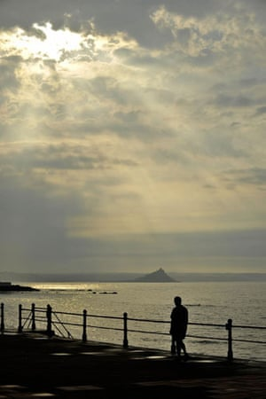 Heatwave: Early morning sunlight breaks through heavy clouds at Penzance