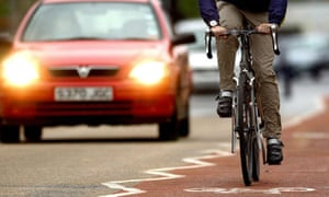 A cyclist using a cycle lane alongside heavy traffic