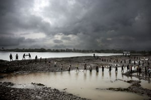 Bangladesh flood defences: Men stand in line, sending mud up to the embarkment