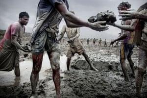 Bangladesh flood defences: Men pass mud along a line