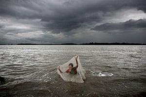Bangladesh flood defences: Men and women fish along the embarkment