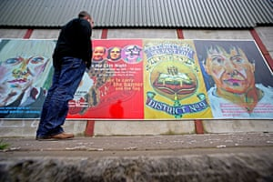 Peace walls in Belfast: A man looks at one of three murals on the loyalist side of the peaceline