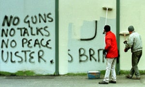 Peace walls in Belfast: Painters whitewash over political graffiti on the Peace Wall