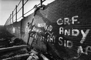 Peace walls in Belfast: Youth Climbing a Dividing Wall